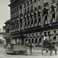 Image: a leisurely scene, with an open horse tram trundling along the road, whilst ladies walk holding sun umbrellas. Two of the ladies are tending to a child in a perambulator. On the right is Eagle Chambers, an imposing three storey building.
