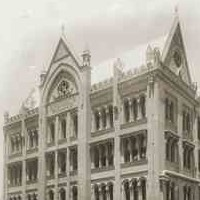 Image: a seven storey gothic style building with a large decorative arch over a protruding verandah on one side, and a line of gable roofs.