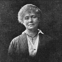 Image: Black and white photograph of woman wearing a dark jacket over a white blouse with a cross around her neck. Her light coloured hair is either pinned back or cut short.