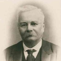 Image: A photographic head-and-shoulders portrait of a middle-aged man wearing a suit and wire-rimmed spectacles