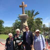 People standing in front of stone cross
