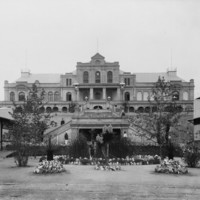 Image: Front view of a historic building with a small garden and trees at the front