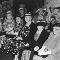 Image: Group of elderly women sitting in a room wearing hats