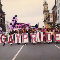"Image: men and women in 1970s era clothes march down a city street with pink and black balloons and signs reading ""gay pride"" and ""homosexual liberation"""
