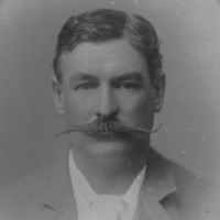 Image: A photographic head-and-shoulders portrait of a man in suit and tie sporting a large handlebar moustache. The frame surrounding the portrait identifies the man as Richard Chaffey Baker
