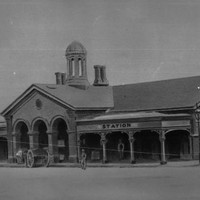 Image: a single storey stone building with pitched cross gable roof, protruding arched portico with verandahs on either side, and an open, octagonal  sided, domed cupola.