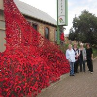 Image: three women standing next to large number of crocheted poppies draped from building