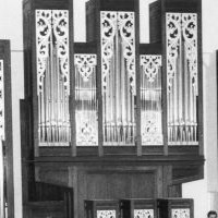 Image: an orchestra plays on a stage in front of a large pipe organ. The organ has two balcony areas within it upon which stand a man and a woman in formal dress.