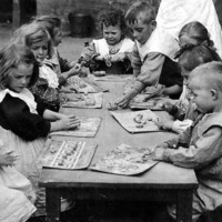 Image: several caucasian children sit around a wooden table playing with plasticine