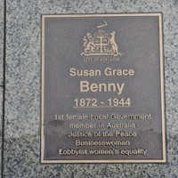 Image: bronze plaque set in pavement inscribed with name and J150 logo