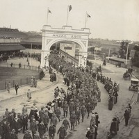 Image: Large group of men in uniform walking through arch and along path